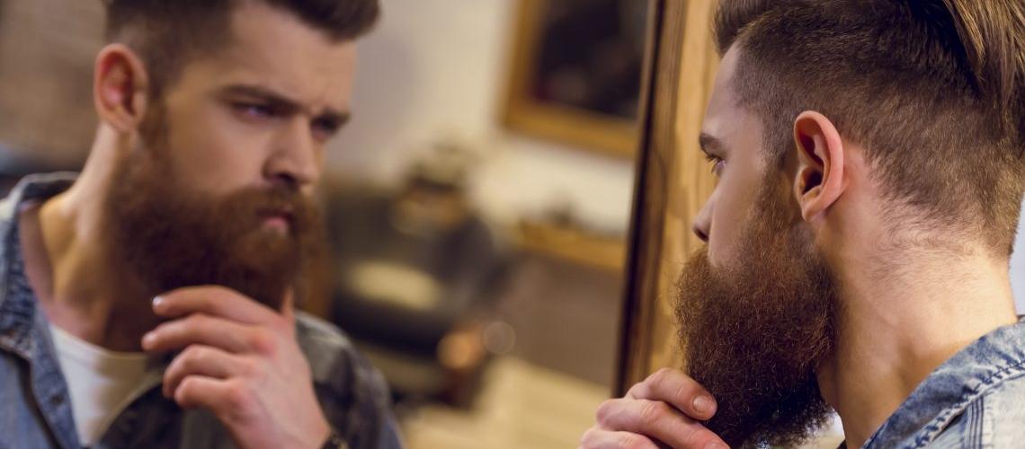 мужчина гладит бороду, глядя в зеркало