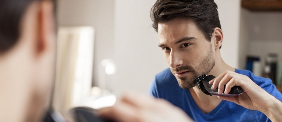 мужчина стрижет бороду электробритвой
