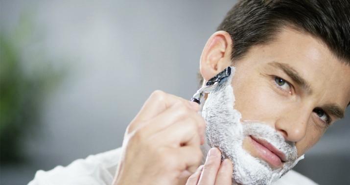 мужчина бреется станком для бритья